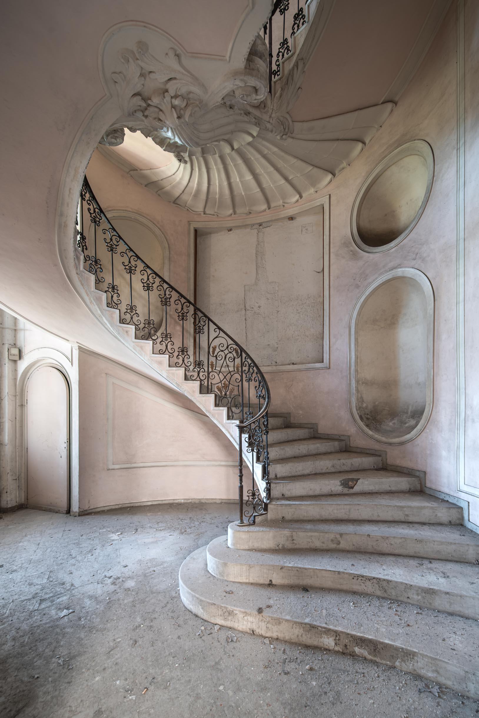 A highly decorated spiral stairwell leading up to the second floor.